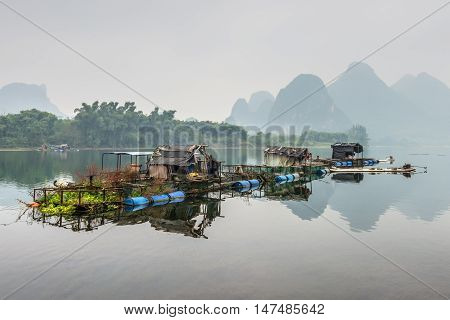 Yangshuo China - October 20 2013: Houses and bamboo raft on the Li river floating island in the overcast nasty day in rural Yangshuo China.