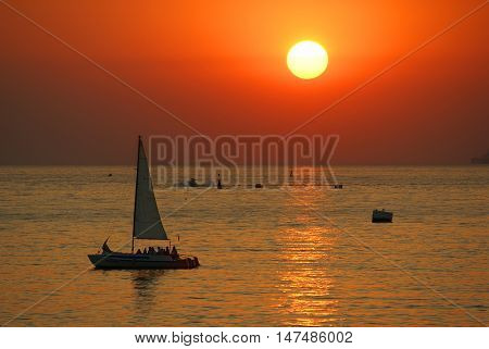 Sunset and a small yatch at the Black sea in Sevastopol Krimea, Russia
