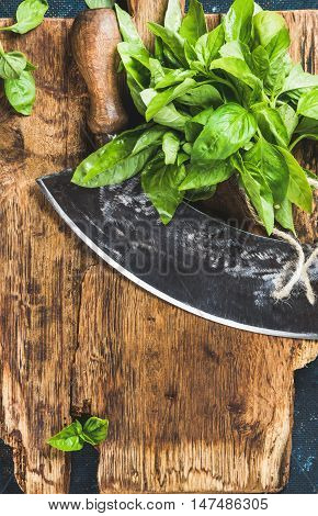 Fresh green basil and vintage herb chopper on rustic wooden bord, top view, copy space, vertical composition