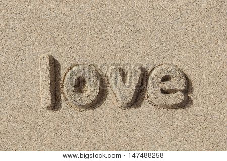 Love written in sand letters. Very simple and graphic.