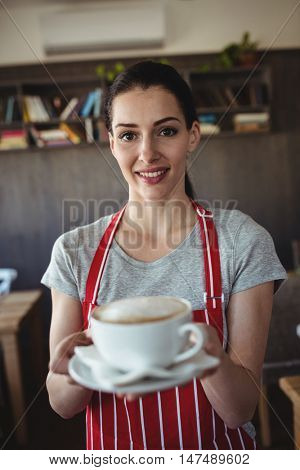 Female baker holding a cup of coffee in baker shop