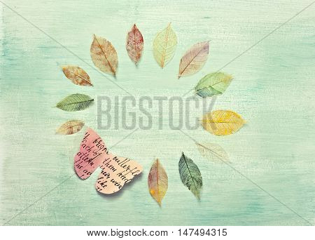 Photo of a frame, made up by hand painted skeleton leaves and a paper butterfly on a teal background texture. A design for an autumn banner, with copyspace