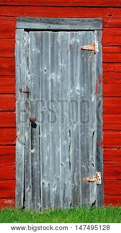 Closeup of smokehouse door. Building is painted red is wooden and has cracked boards and worn paint.