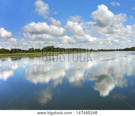 Reflection of sky and clouds causes you to see double as the surface of the Yahara River serves as a mirror for the scenery on the Yahara River Trail in Wisconsin.