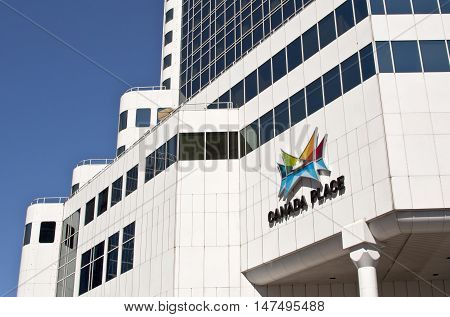 Vancouver, BC - April 20, 2015 - Canada Place from the Howe St. entrance on a sunny day, featuring the colourful sign over the entrance and a wide view of the pure white facade and smokey glass windows of the structure's beautiful architecture. Slightly s