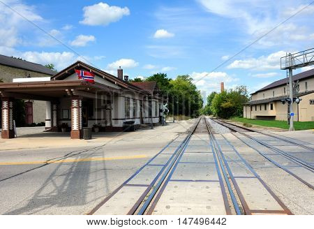 Image taken from center of tracks shows them disappearing into the distance. Old historic train depot sits besides tracks in Stoughton Wisconsin.