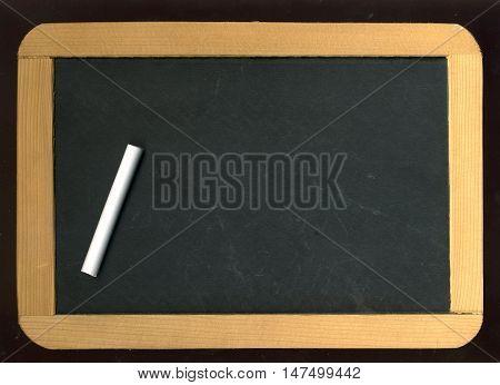Image of little blackboard and chalk on black background