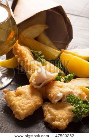 Traditional British fish and chips on the black background with glass of beer