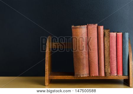 A row of old used books with blank spines upright on a desktop shelf with black chalkboard background.