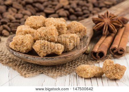 Brown sugar in a wooden spoon on the old wooden table. Selective focus.