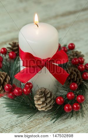 Burning candles in a Christmas setting with seasonal decorations.