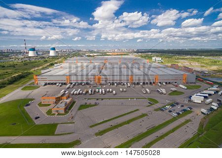 Aerial view of distribution hub. Next to them a few trucks waiting for loading. The building is gray with red accents. Russia, 2016