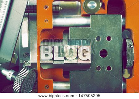 blog word made from metallic font fixed inside complicated mechanical system