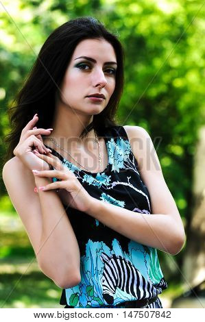 Young pretty woman posing in summer day over nature background