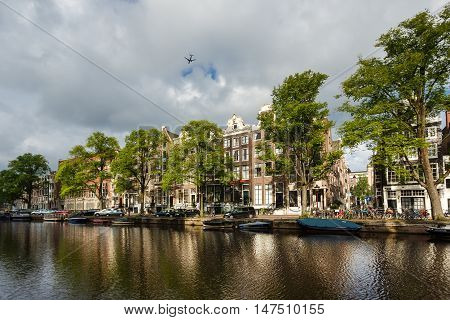 Amsterdam Netherlands - July 03 2016: The airplane over the traditional Dutch houses reflected in water on Singel street sunny morning