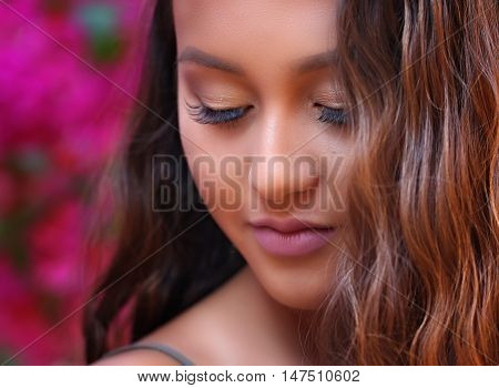 Beautiful girl looking down with pink floral background