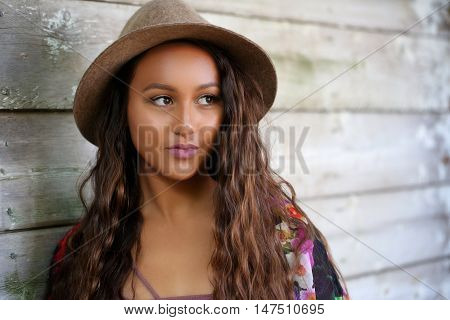 Pretty girl with long, wavy hair, standing against an old wood wall outdoors wearing a hat on her head