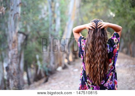 Young girl with long hair on a dirt path looking off into the distance