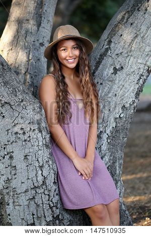 Young, pretty, suntanned, happy girl standing near trees