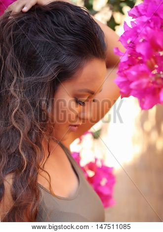 Girl standing near bougainvillea outside in a garden