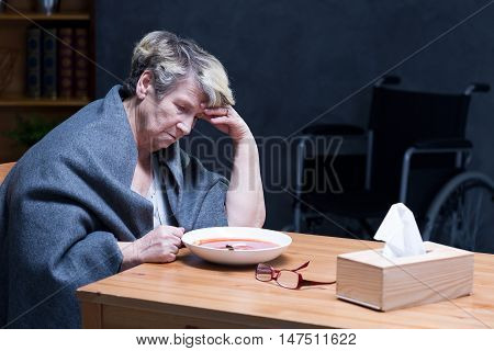 Lonely woman sitting at the table with the wheelchair at the background