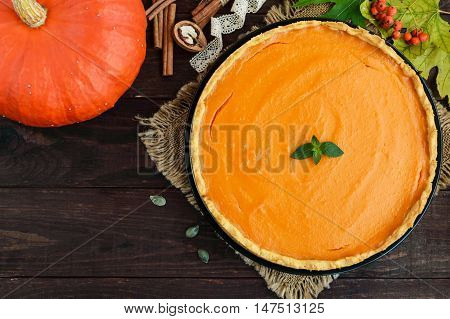 Sweet pumpkin pie on a dark wooden background. The top view. Dietary vegan dish. Traditional baked for Thanksgiving.