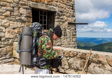 Portrait of young men tourist in the old observatory on the top of Pip Ivan mountain Carpathians summertime journey