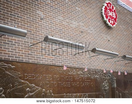 NEW YORK - SEPT 9 2016: Wreath of red flowers shaped as FDNY badge and bronze bas-relief Memorial Wall at the FDNY Ten House fire station before the 15th anniversary of the terror attack at the WTC.