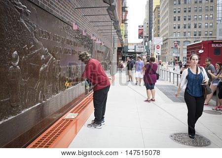NEW YORK - SEPT 9 2016: A man cleans the bronze bas-relief Memorial Wall at FDNY Ten House fire station before the 15th anniversary of the terror attack at the WTC across the street.