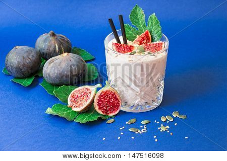 Glass of fig fruit smoothie fig slices straws and near scattered sunflower susami seeds ripe fig fruits on the fig tree leaves on blue background. Fig fruit smoothie glass. Horizontal. Daylight.