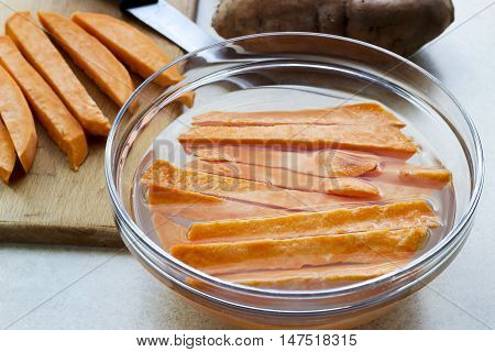Sweet Potatoes Slices In A Bowl With Water