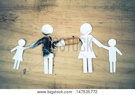 paper cut of family members destroyed by cigarettes / drugs destroying family concept