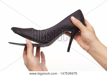 Female hand holding broken high heel shoes