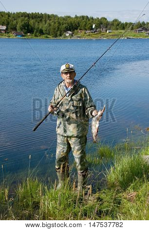 fisherman with a fishing rod and fish on the lake