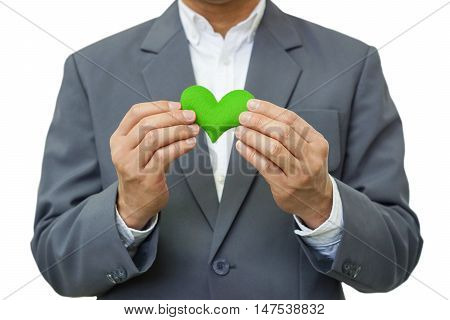 Businessman holding a green heart / Business with corporate social responsibility and environmental concern