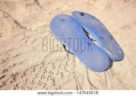 Flip Flops Upturned On Beach Sand Insunshine