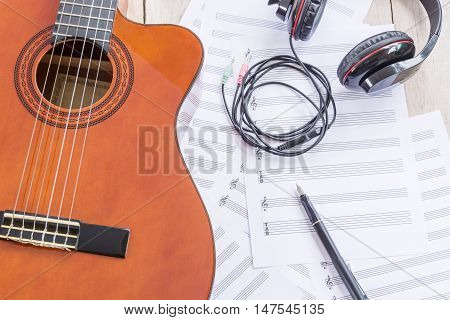 Acoustic guitar, music paper, big earphone, fountain pen on wooden table
