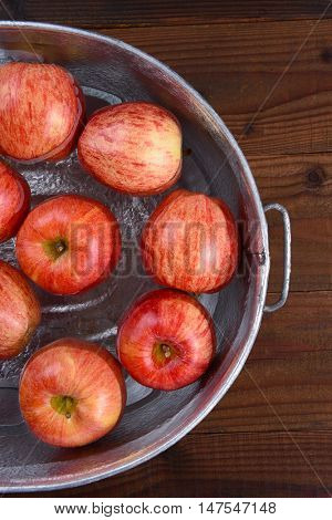 High angle vertical closeup of a metal tub filled with water and apples for the Halloween custom of Apple Bobbing.