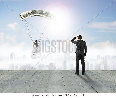 Businessman Gazing Light Bulb With Money Parachute