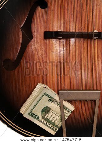Detail view of old beat-up acoustic guitar with a wad of U.S. paper money stuck in the tailpoece.