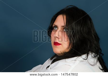 young beautiful brunette in a white shirt on a dark background