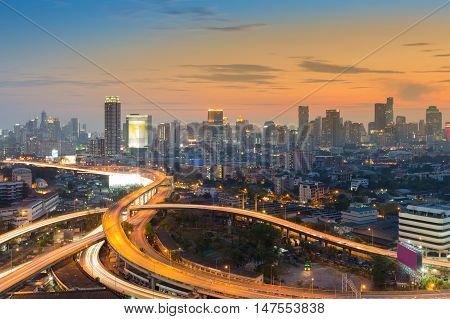 Sunset sky over highway interchange with city central business background, Bangkok Thailand