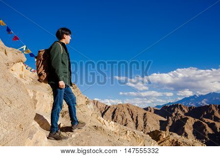 Young Asian Traveler Standing On High Hills And Looking Away At The Village Over Blue Sky Background