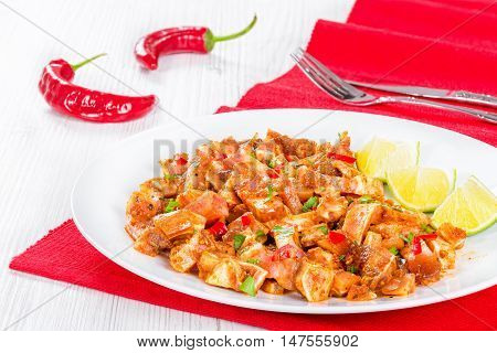 cooked and marinated Pig Ears or Oreja de Cerdo with spices chili pepper pieces of lime sprinkled with parsley on white platter on wooden old boards top view