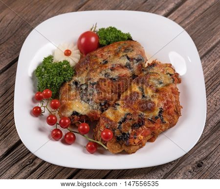 Baked chicken breasts with garnish on the old wooden surface