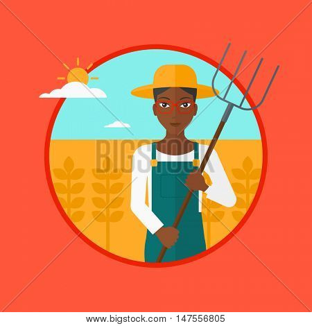 An african-american farmer standing with a pitchfork in wheat field. Woman holding agricultural tool and working in wheat field. Vector flat design illustration in the circle isolated on background.