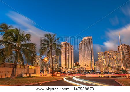 Luxurious hotels overlooking the Ala Wai Harbor at twilight and the light trails in Honolulu Oahu Hawaii.
