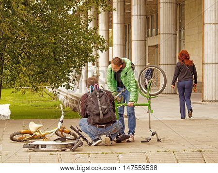 MOSCOW, RUSSIA - September 4, 2016: Man in the squatting position with a backpack with two umbrellas corrects the malfunction of an inverted bicycle in the park Museon. Standing mid adult woman watching his actions. September 4, 2016 in Moscow, Russia