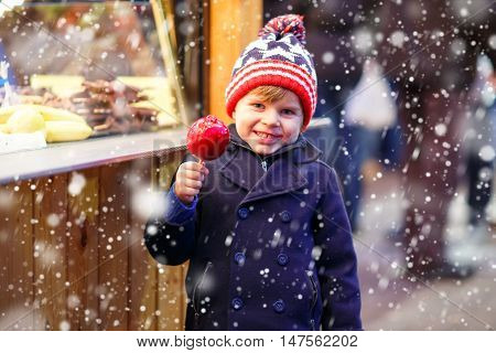 Cute little kid boy eating crystalized sugared apple on German Christmas market. Happy child in winter clothes  with lights on background. Kid looking at the camera. Family, tradition, holiday concept