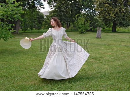 European woman dancing and touching her hat in vintage dress in park. White color, curly hair, sensitive, sensuality.